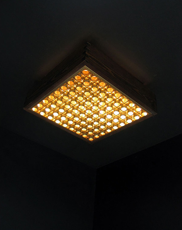 Wooden ceiling lamp illuminated behind grating Wabbes