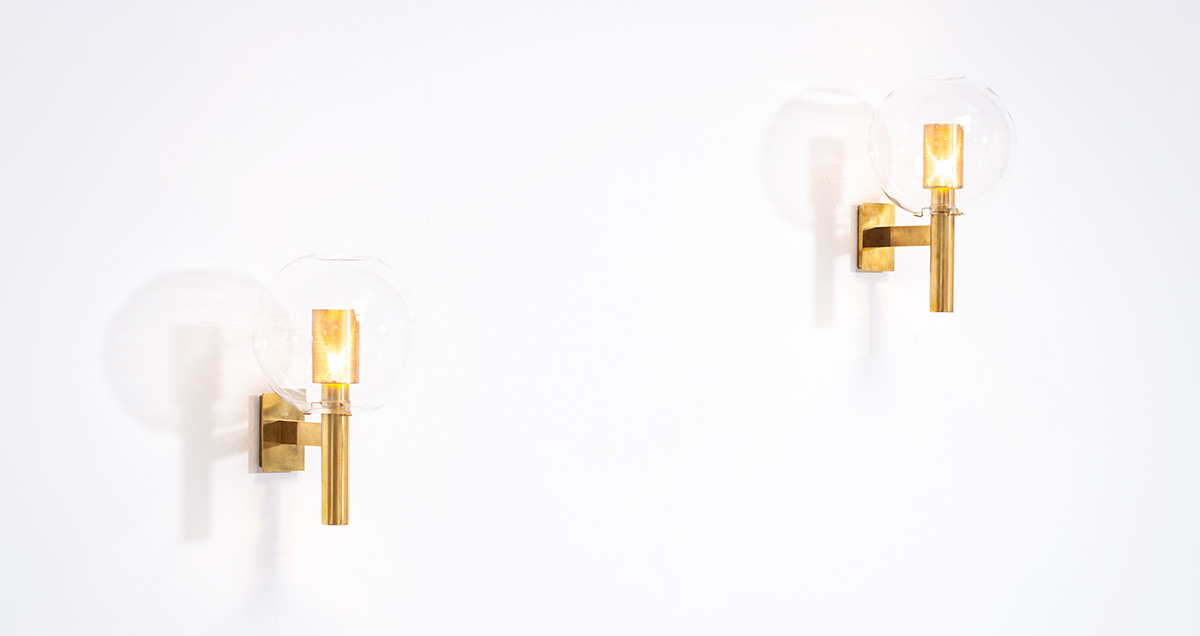 Pair of wall sconces. Model V80, designed in 1959 by Hans Agne Jakobsson for Hans-Agne Jakobsson AB Markaryd. Light fixtures each featuring a clear glass globe with inside a brass body with perforated brass light diffuser. The combination of the warm vibrance of the brass and the glass spheres forms a beautiful combination.